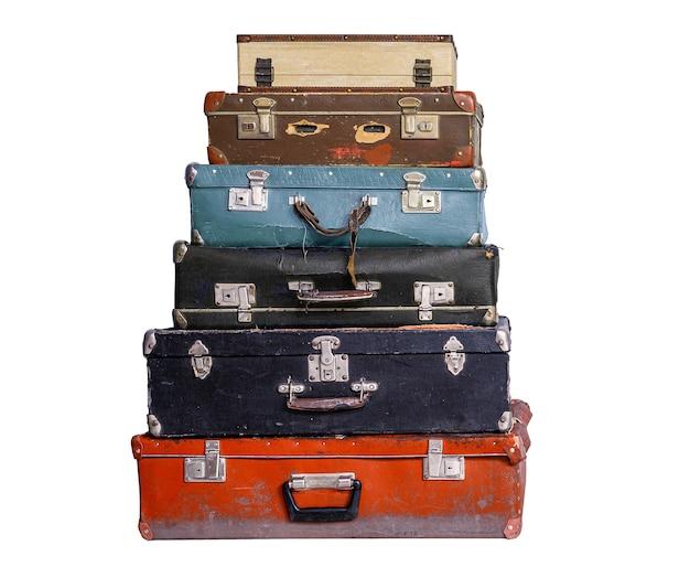 Pila di vecchie valigie vintage multicolori isolate su sfondo bianco.
