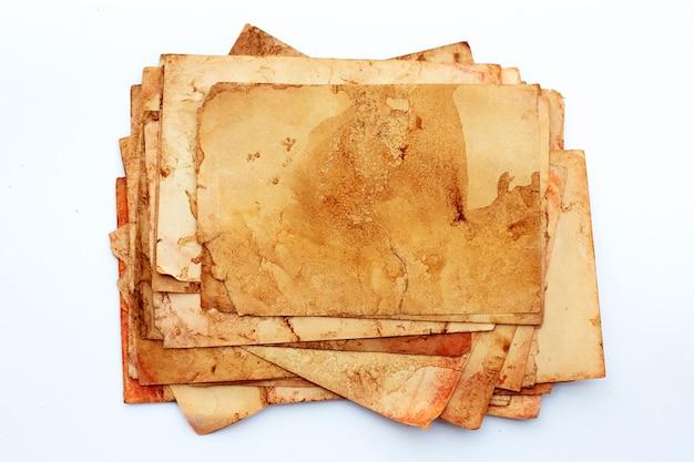 Pila di vecchie carte isolate su superficie bianca.