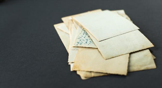 Una pila di vecchie foto che giace sul tavolo. carta fotografica vintage sgualcita e sporca.