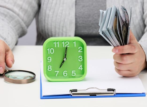 Pila di banconote da cento dollari in mano di una donna e una lente d'ingrandimento in legno su un tavolo bianco. analisi budget, entrate e uscite, problem solving