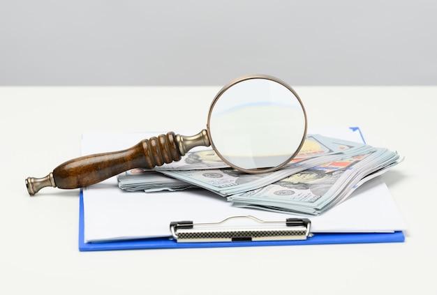 Una pila di banconote da cento dollari e una lente di ingrandimento in legno su uno sfondo bianco. analisi budget, entrate e uscite, problem solving