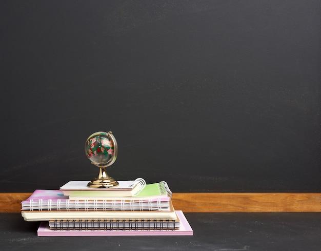 Pila di taccuini della scuola di carta e globo di vetro sullo spazio nero del bordo di gesso
