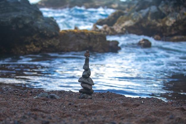 Pila di ciottoli di pietra sullo sfondo del mare per la meditazione sull'equilibrio della spa e il tema zen