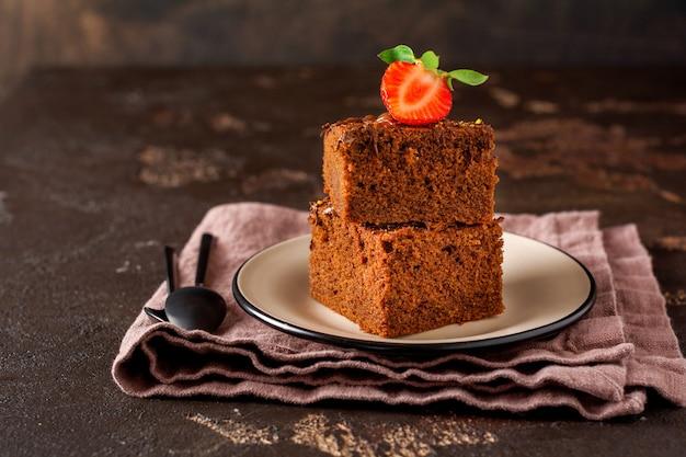 Pila di pezzi o barretta di torta al cioccolato brownie con fragole e noci su nero