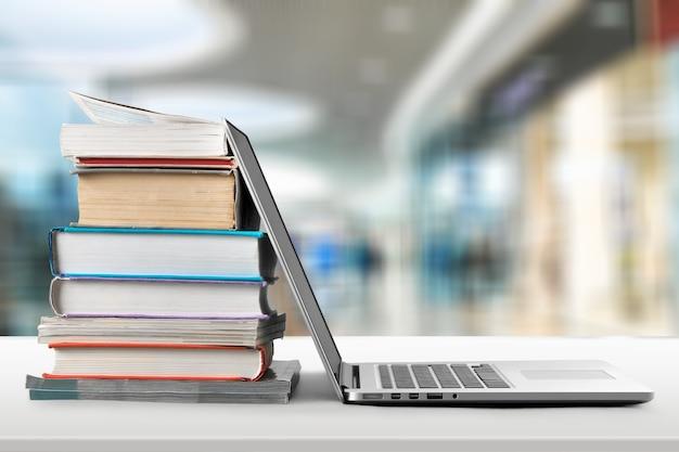 Pila o pila di libri con il computer portatile sul tavolo di legno. posto di lavoro per il lavoro