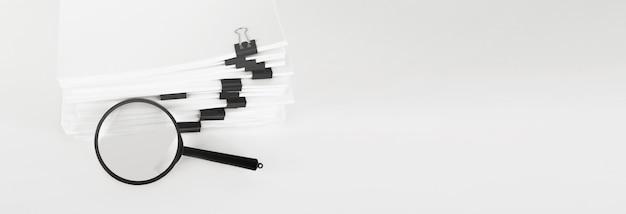 Pila di documenti cartacei con lente d'ingrandimento. concetto di affari e ricerca.