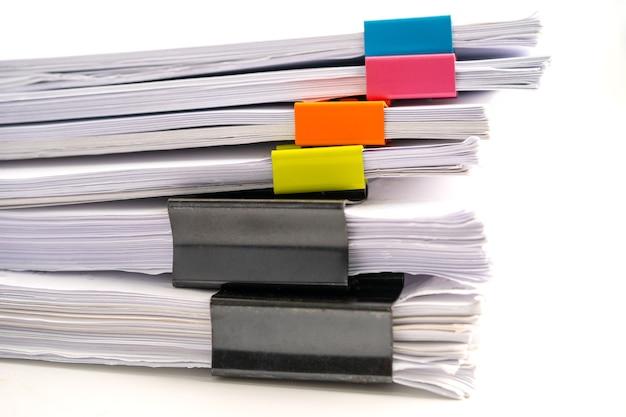 Pila di file cartacei di relazione nelle clip dell'ufficio commerciale.