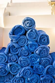Pila di asciugamani blu arrotolati