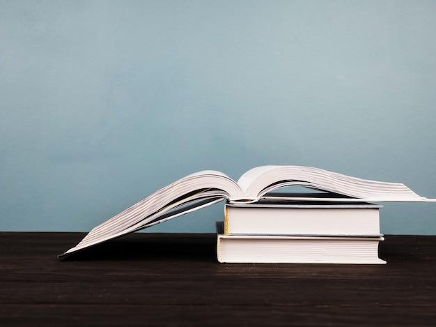 Una pila di parecchi libri, primo piano, libro aperto nella priorità alta.