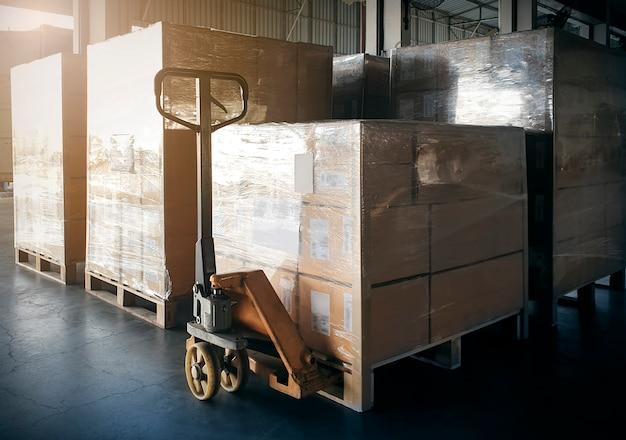 Pila di scatole delle spedizioni sui pallet di legno a stoccaggio interno del magazzino.