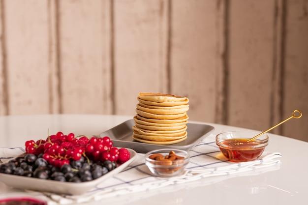 Pila di piccole frittelle fatte in casa sulla piastra, ribes rosso maturo fresco e more, piccole ciotole di vetro con miele e mandorle