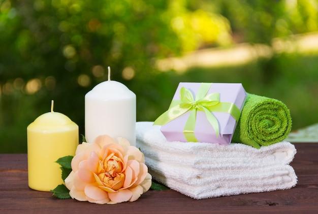 Pila di morbidi asciugamani, rosa profumata, candela e scatolina con regalo.