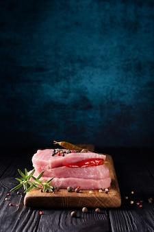 Pila di bistecche di carne di maiale cruda fresca decorata con peperoncino e rosmarino al buio.