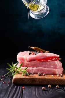 Pila di bistecche di carne di maiale cruda fresca decorata con peperoncino e rosmarino con azione dello chef versando olio d'oliva su un buio.