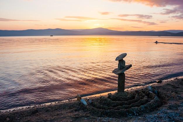 Pila di pietre sulla spiaggia al tramonto skyline