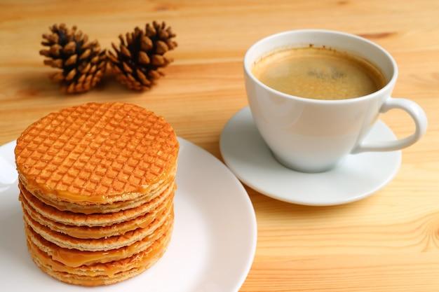 Pila di stroopwafel e una tazza di caffè caldo con pigne