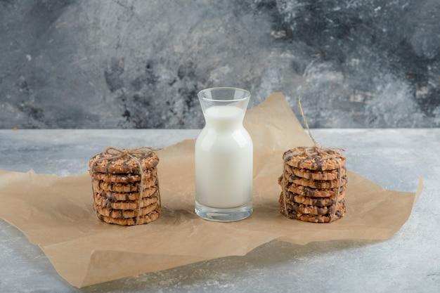 Pila di gustosi biscotti con semi e cioccolato e latte su marmo.