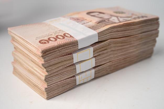Pila di banconote in baht thailandese su bianco