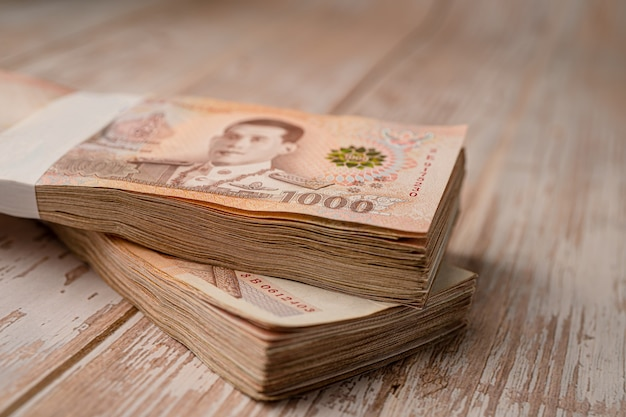 Pila di baht thailandesi banconote su una superficie di legno