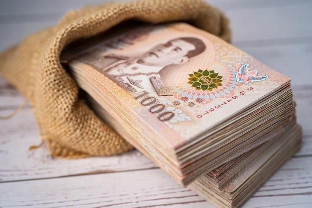 Pila di baht thailandesi banconote sulla tavola di legno, concetto di investimento finanziario di risparmio aziendale.