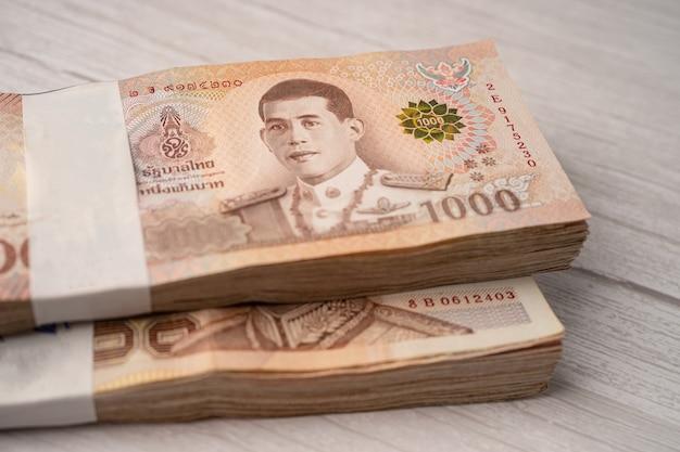 Pila di banconote di baht tailandesi sulla tavola di legno, concetto di investimento di finanza di risparmio di affari.