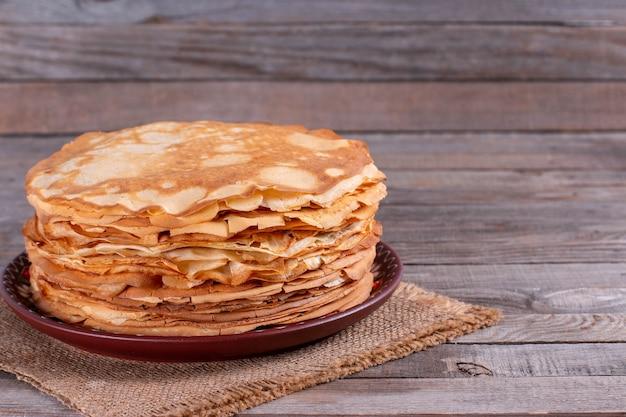 Pila di frittelle sottili in un piatto su un tavolo di legno