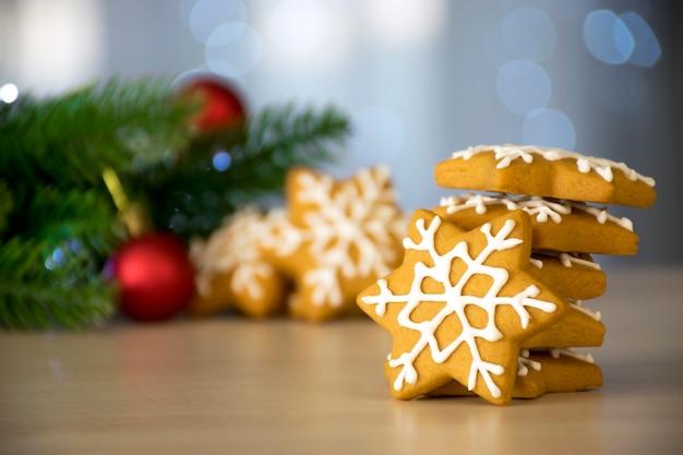Pila di panpepato tradizionale dei biscotti di natale a forma di fiocco di neve con glassa bianca con rami di abete