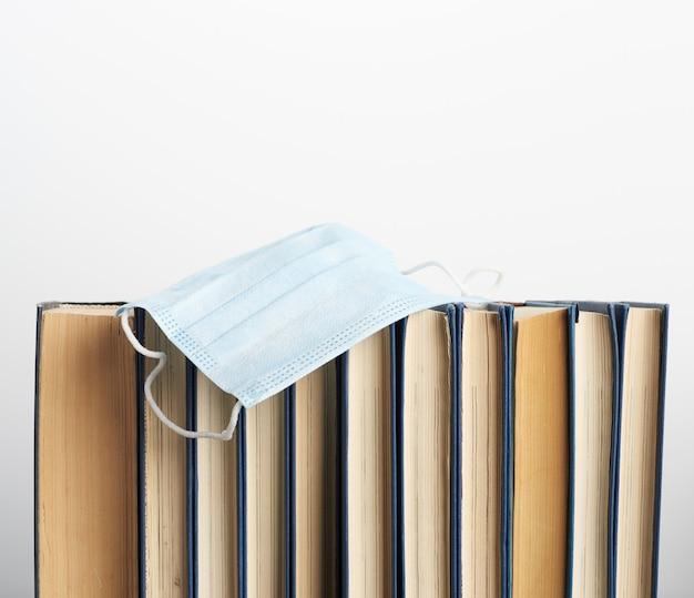 Pila di vari libri e maschere mediche usa e getta
