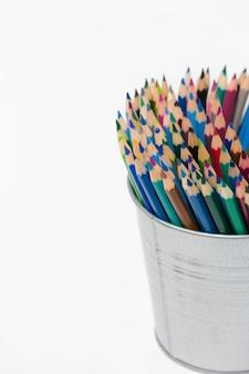 Pila di varie matite di colore in un barattolo di latta su fondo bianco