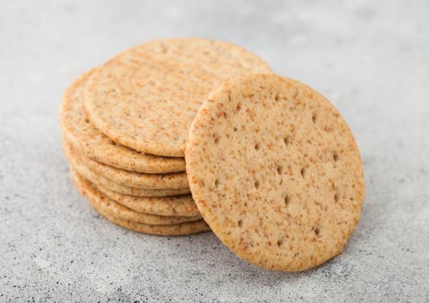 Pila di vari cracker di frumento croccanti organici con sesamo e sale su sfondo chiaro.