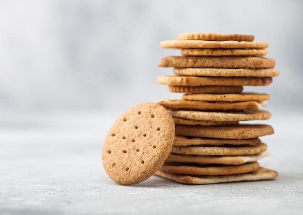 Pila di vari cracker croccanti organici di grano, segale e mais con sesamo e sale su sfondo chiaro. spazio per il testo