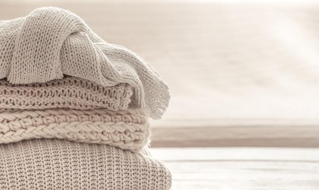Una pila di articoli lavorati a maglia caldi sullo spazio bianco vago della copia del fondo.