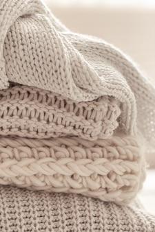 Una pila di articoli a maglia caldi su sfondo bianco sfocato.