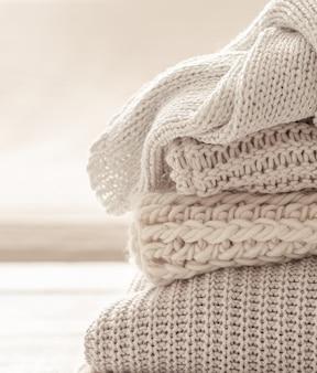 Una pila di articoli lavorati a maglia caldi su sfondo bianco sfocato.