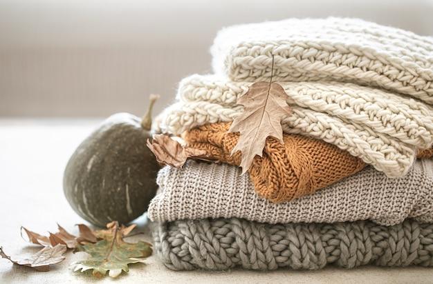 Pila di caldi articoli lavorati a maglia dal guardaroba autunnale e zucca si chiuda.
