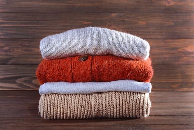 Pila di vestiti invernali caldi su una superficie di legno