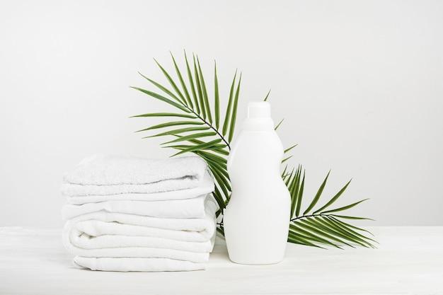 Una pila di biancheria bianca e una bottiglia di detersivo per bucato con foglie di palma bianca o ammorbidente. mockup di giorno di lavanderia tropicale.