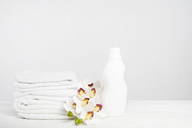 Pila di biancheria bianca, gel di lavaggio e ammorbidente su un tavolo bianco con fiori di orchidea. giornata di lavanderia mockup in un hotel tropicale con copia spazio.