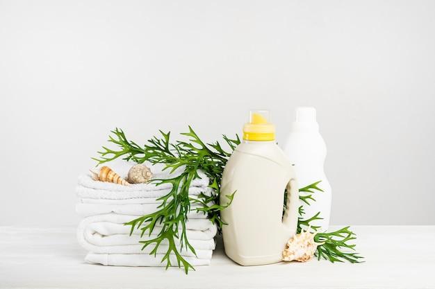 Una pila di biancheria bianca, gel di lavaggio e ammorbidente su un tavolo bianco con alghe e conchiglie. giornata di lavanderia mockup in un hotel tropicale. bottiglia di detersivo liquido.