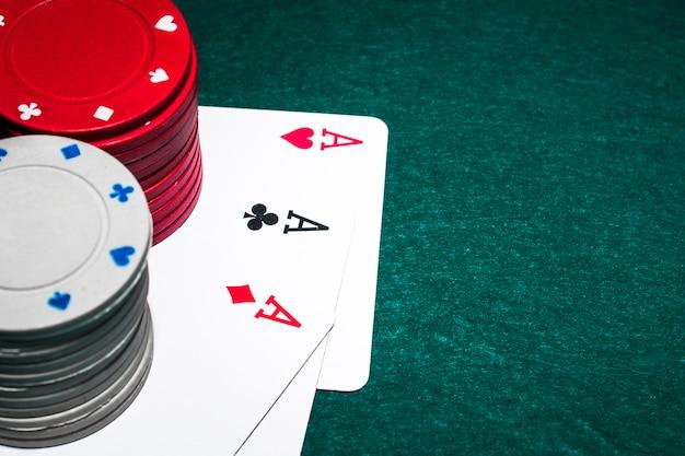 Pila di fiches del casinò bianco e rosso sopra i tre assi sul tavolo da poker