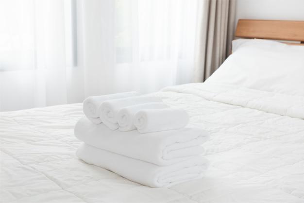 Pila di asciugamani bianchi sul letto bianco nella camera da letto moderna