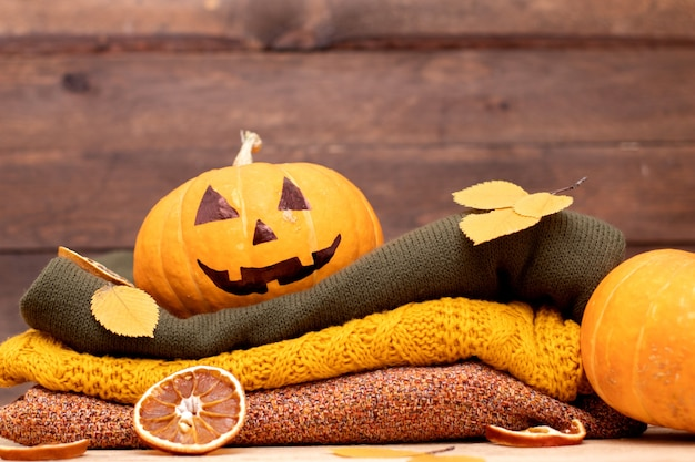 Pila di maglioni invernali e lanterna della presa della testa della zucca di halloween su fondo di legno.
