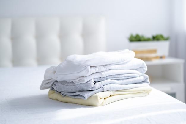 Pila di felpe colorate da donna, felpe con cappuccio in colori pastello sul letto bianco. shopping stagionale, lavanderia, concetto di vacanza.