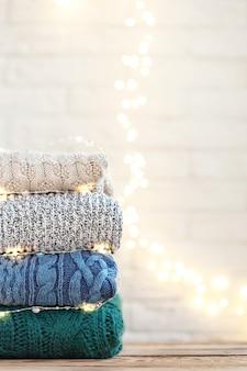 Pila di vestiti lavorati a maglia di lana su sfondo wite con bokeh festivo.