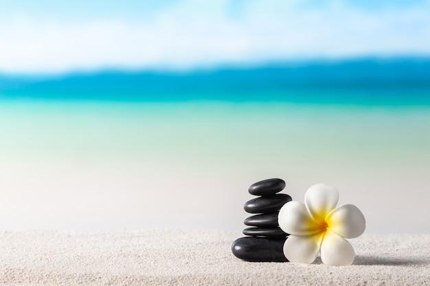 Pila di pietre zen e fiori sulla spiaggia di sabbia