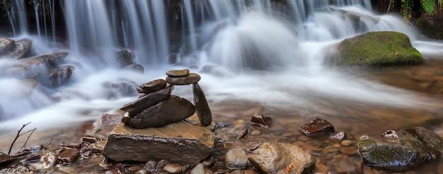 Rocce equilibrate impilate sulla cascata del fiume della montagna Foto Premium