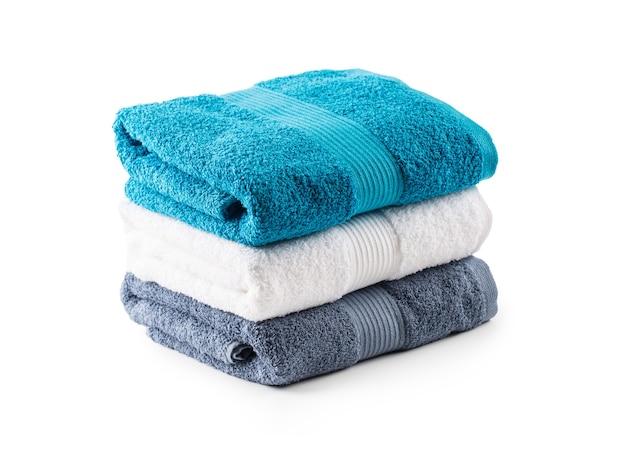 Asciugamani bianchi e grigi blu impilati isolati su bianco.