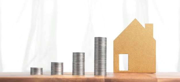 Monete impilate e modello di casa