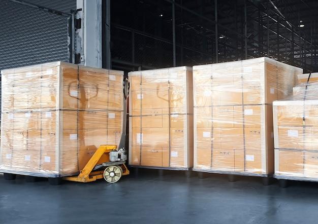 Impilati di scatole da imballaggio in plastica avvolta su scaffalature per pallet interno del magazzino di stoccaggio magazzino di spedizione logistica di carico esportazione e importazione