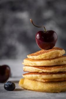 Frittelle impilate con ciliegie e mirtilli su un tavolo di legno grigio vintage spazio per il testo